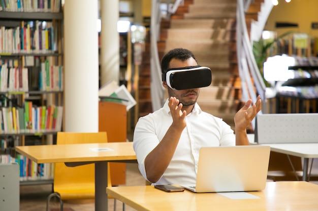 Fokussierter kerl mit vr-kopfhörer, der in der bibliothek sitzt
