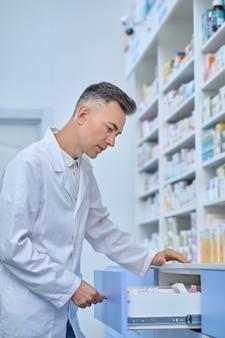 Fokussierter männlicher apotheker, der ein medikament für seinen kunden auswählt