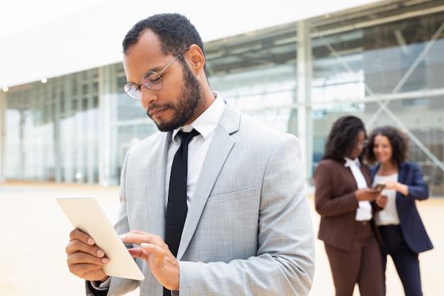 Fokussierter männlicher geschäftsfachmann, der tablette verwendet