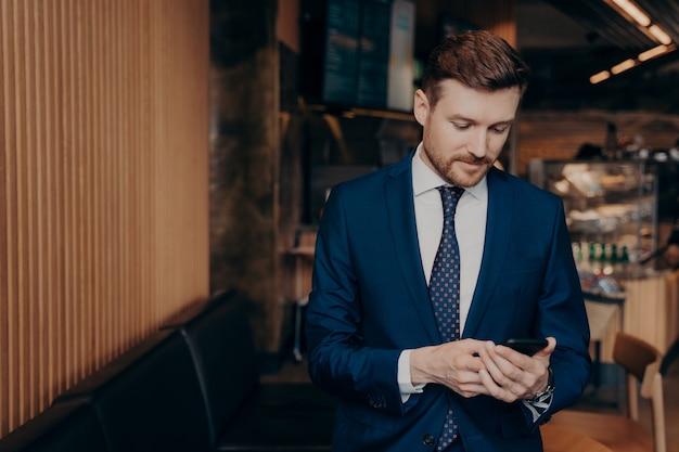 Fokussierter männlicher investor im blauen anzug, der über börsenkurse informiert wird, sein telefon überprüft, nachrichten ansieht und entscheidet, ob er investieren soll oder nicht, allein im café stehen