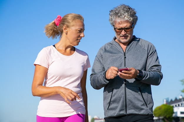Fokussierter männlicher jogger mit fitness-app auf dem handy nach dem joggen. reifes paar, das sportkleidung trägt und draußen steht. kommunikation und gadget für sportkonzept
