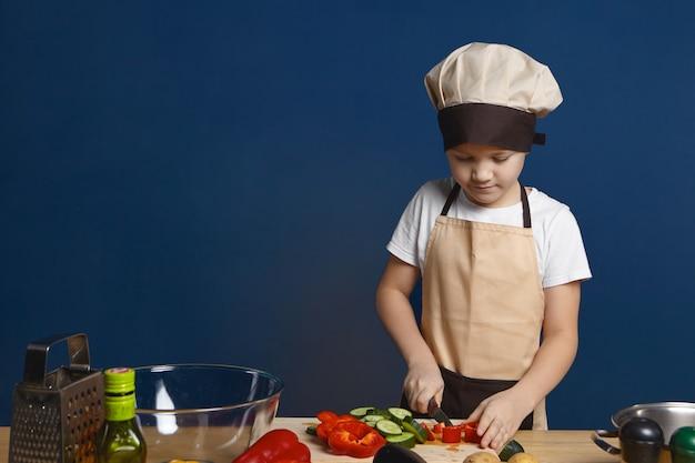 Fokussierter männlicher kinderkoch in der schürze und im hut, die gemüse für vegetarische lasagne schneiden