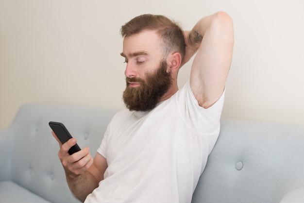 Fokussierter mann, der auf smartphone grast und auf sofa sitzt