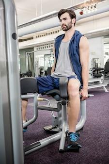 Fokussierter mann, der gewichtsmaschine für beine an der turnhalle verwendet