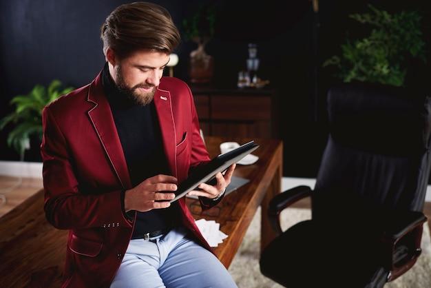 Fokussierter mann, der im home office mit digitalem tablet arbeitet