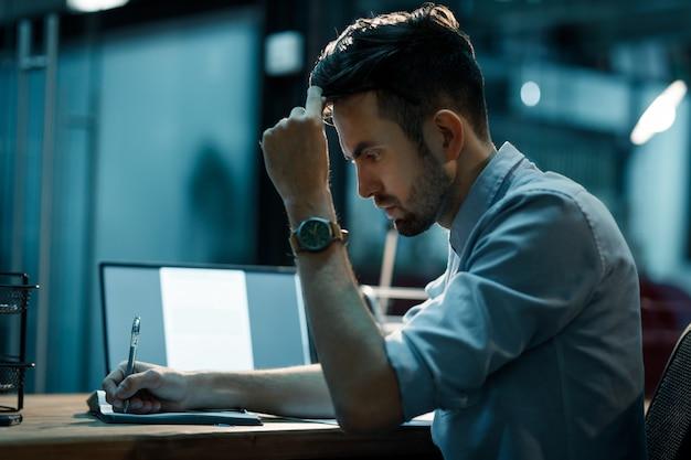 Fokussierter mann, der im notizblock schreibt