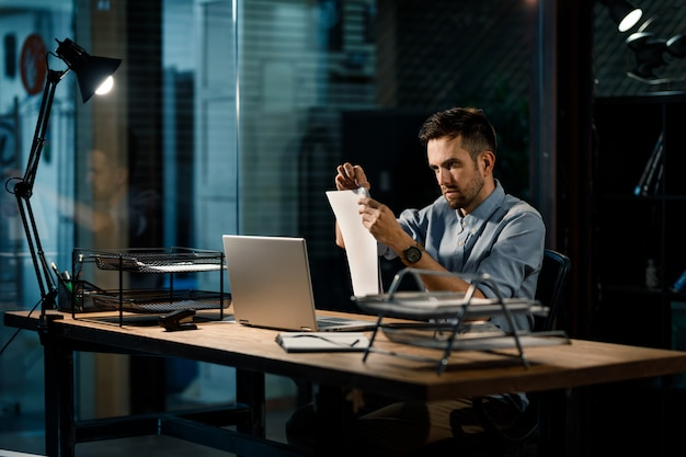 Fokussierter mann, der papiere mit clip befestigt