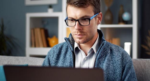 Fokussierter mann in brillen und freizeitkleidung unter verwendung des laptops, der bildschirm betrachtet, der auf sofa in der wohnung sitzt