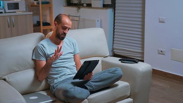 Fokussierter mann mit bart sitzt auf der couch vor dem fernseher