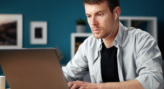 Fokussierter mann mit laptop, zu hause