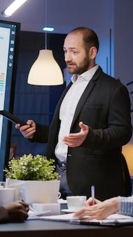 Fokussierter mannführer, der das managementprojekt mit dem monitor erklärt, der im büroraum des unternehmens...