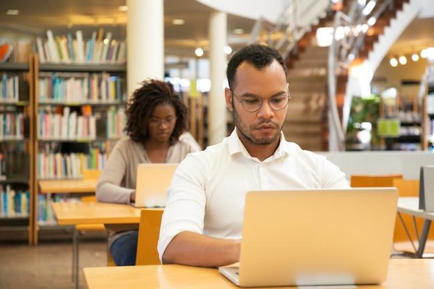 Fokussierter mannstudent, der an computer arbeitet