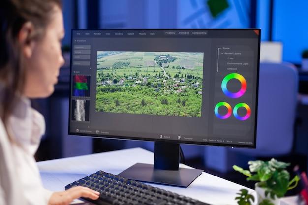 Fokussierter redakteur, retuscheur, der den farbgrad auf einem professionellen computer bearbeitet, der um mitternacht am schreibtisch im kreativbüro sitzt