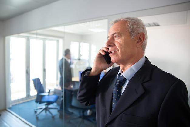 Fokussierter reifer geschäftsmann, der auf handy an der büroglaswand spricht und im korridor steht. kommunikationskonzept