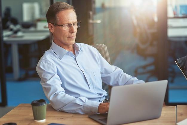 Fokussierter reifer geschäftsmann im blauen hemd mit laptop während der arbeit im modernen büro