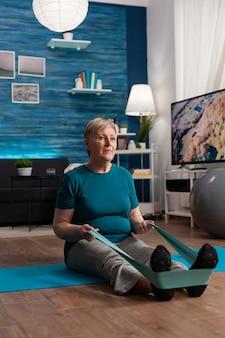 Fokussierter rentner mit sportkleidung, der auf einer yogamatte sitzt und den beinmuskel ausdehnt