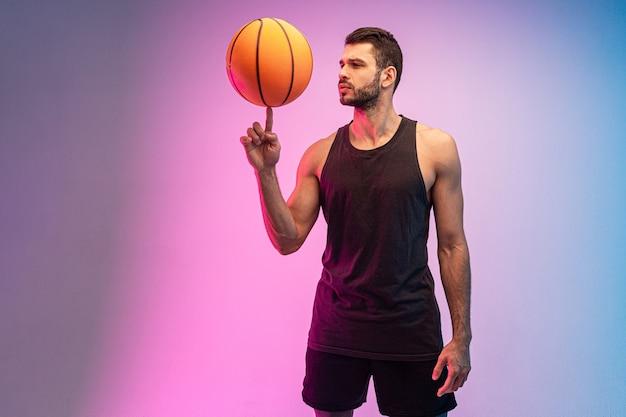 Fokussierter sportler, der basketballball auf finger dreht. junger bärtiger europäischer basketballspieler. getrennt auf blauem und rosa hintergrund. studio-shooting. platz kopieren