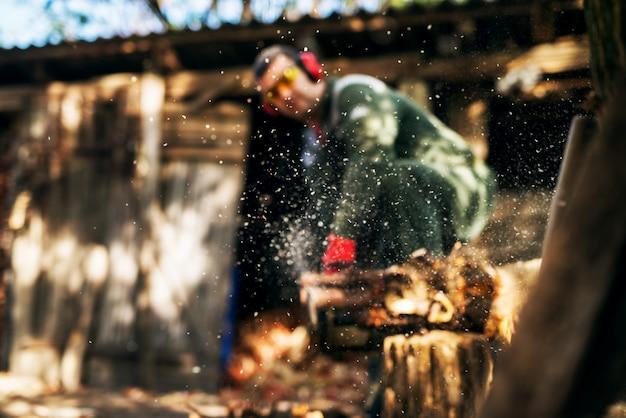 Fokussierter staub beim holzfällerarbeiten mit kettensäge