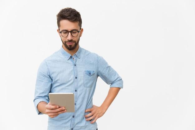 Fokussierter tablet-benutzer, der inhalte auf dem bildschirm liest
