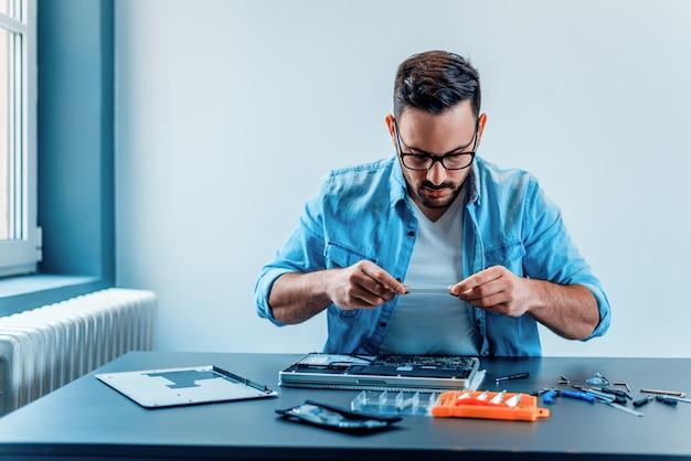 Fokussierter techniker, der auseinandergebaute laptop-hardware fotografiert