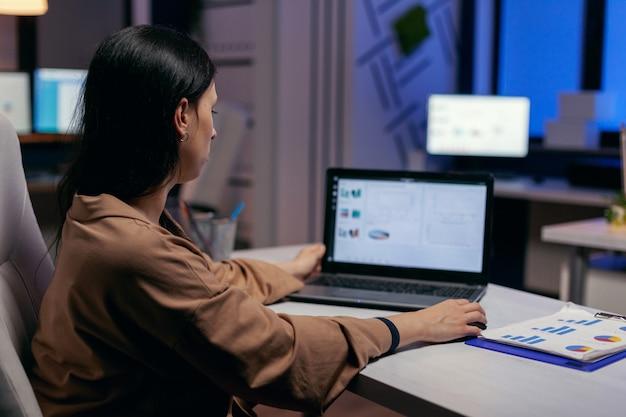 Fokussierter unternehmer, der geschäftsberichte überprüft, die versuchen, eine frist zu beenden. geschäftsfrau, die statistiken über den laptop-bildschirm betrachtet, der an ihrem arbeitsplatz sitzt und überstunden macht.