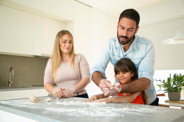 Fokussierter vater, der tochter lehrt, teig auf küchentisch mit mehl unordentlich zu machen. junge eltern und ihr mädchen backen zusammen brötchen oder kuchen. familienkochkonzept