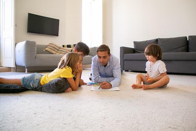Fokussierter vater und kinder, die auf teppich liegen und auf papier malen. liebender kaukasischer vater, der mit markern zeichnet und mit niedlichen kindern zu hause spielt. konzept für kindheit, spielaktivität und vaterschaft