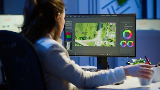 Fokussierter videofilmer, der film auf professionellem computer bearbeitet, der um mitternacht am schreibtisch im geschäftsbüro sitzt. kreativer videoeditor, der nachts bei der verarbeitung von audiofilmmontagen für neue projekte arbeitet.