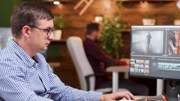 Fokussierter videofilmproduzent, der in der filmproduktion arbeitet und filmdesign bearbeitet