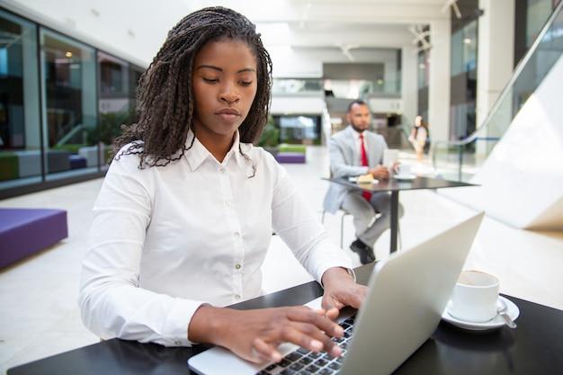 Fokussierter weiblicher manager, der an laptop arbeitet