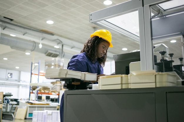 Fokussierter weiblicher papierfabrikangestellter, der helm trägt, industriemaschine bedient, an der steuerplatine steht