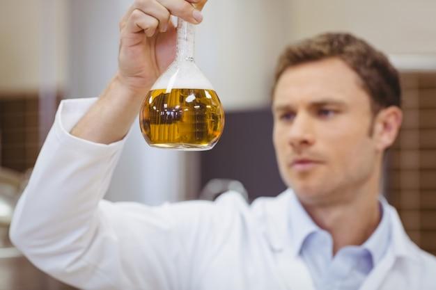 Fokussierter wissenschaftler, der becher mit bier hält