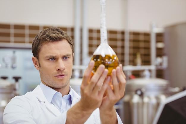 Fokussierter wissenschaftler, der becher mit bier schaut