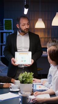 Fokussierter workaholic-unternehmermann, der überstunden macht und unternehmensstatistiken mit tablet präsentiert. diverse multiethnische geschäftsleute, die spät in der nacht im besprechungsraum im büro überarbeiten
