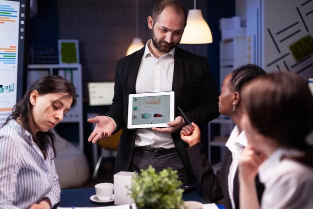 Fokussierter workaholic-unternehmermann, der überstunden macht und unternehmensstatistiken präsentiert