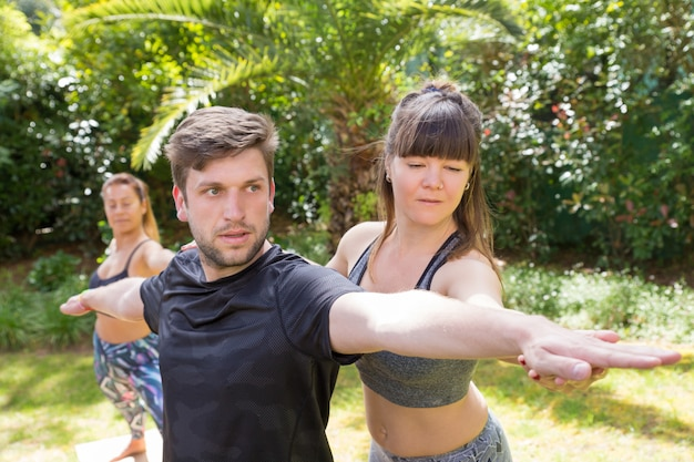 Fokussierter yogalehrer, der newby hilft
