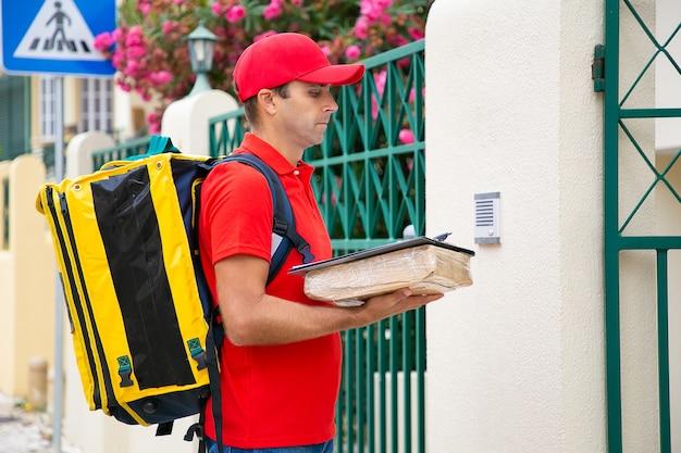 Fokussierter zusteller, der die adresse liest und auf den kunden in der nähe des eingangs wartet. kaukasischer postbote, der paket und zwischenablage hält, draußen steht und auftragsdaten liest. lieferservice und postkonzept