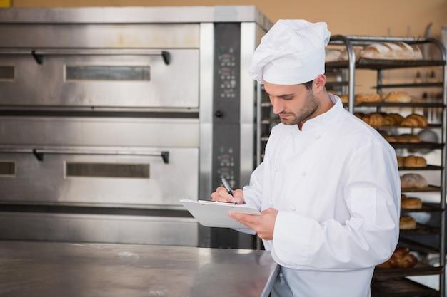 Fokussiertes bäckerschreiben in der zwischenablage