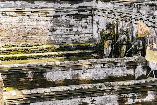 Fokussiertes foto auf brunnen, der mit alten statuen geschmückt ist, sonne scheint auf grünes wasser