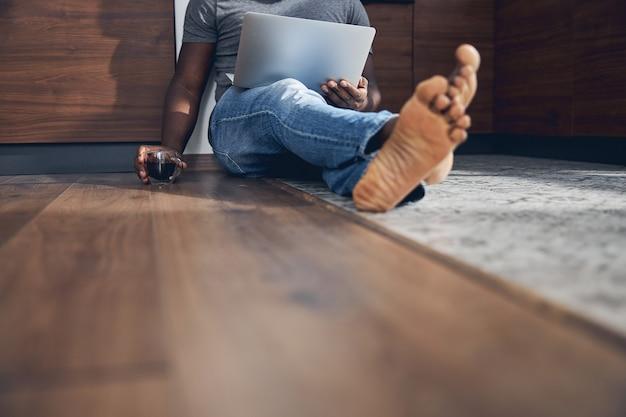 Fokussiertes foto auf einem entspannten mann, der einen laptop auf den knien hält und eine tasse nimmt, während er kaffee trinkt