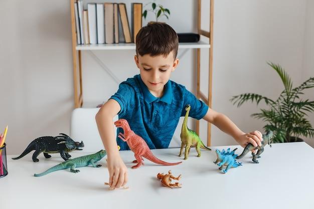 Fokussiertes kind, das zu hause mit dinosauriern spielt. junge lernt paläontologie von dino-spielzeug in der freizeit. konzept der klugen kinder- und früherziehung