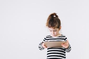 Fokussiertes Mädchen, das Tablette verwendet