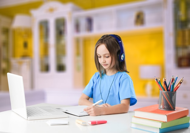 Fokussiertes teenager-mädchen mit kopfhörern, das notizen schreibt und hausaufgaben macht