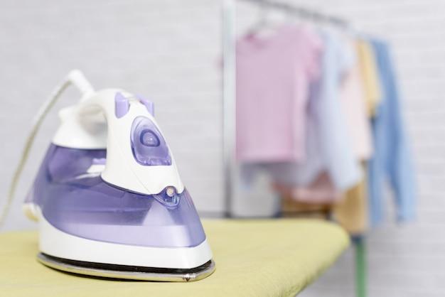 Fokussiertes violettes eisen platziert auf bügelbrett