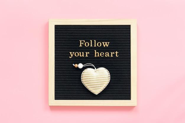Folge deinem herzen. motivzitat in den goldbuchstaben und im dekorativen textilherzen auf brett der schwarzen schrift auf rosa hintergrund.