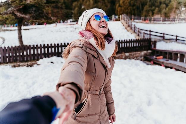 Folge mir. glückliche frau und mann, die hände halten. pov. wintersaison am berg. liebeskonzept