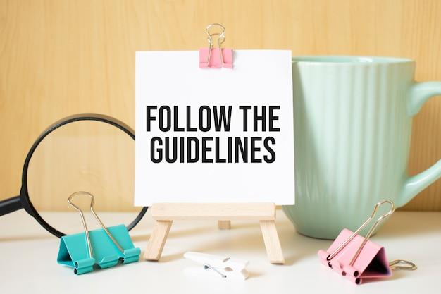 Folgen sie den richtlinien text auf schwarzem notizbuch mit lupe und stift geschrieben. geschäfts- und leistungskonzept.