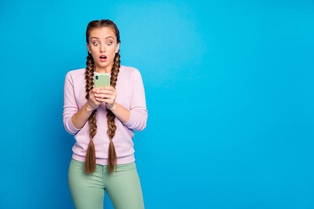 Follower mögen keinen blog-beitrag! porträt der frustrierten emotionalen jugend verrückte mädchen aussehen sprachlos ihr smartphone bekam schreckliche social-media-sms tragen grüne hosen hose isoliert hellen farbhintergrund