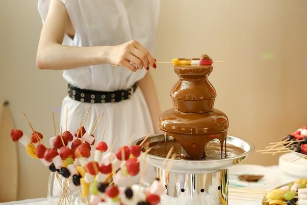Fondue mit schokoladenbrunnen und süßigkeiten dafür. süßes thema.