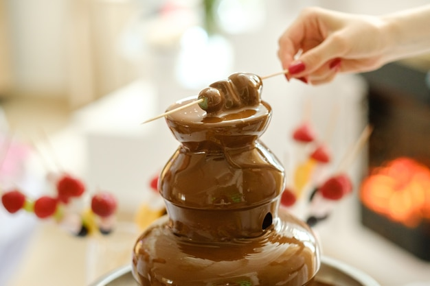 Fondue mit schokoladenbrunnen und süßigkeiten dafür. süßes thema